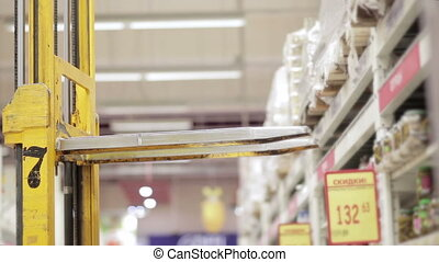 forklift trucks loads the goods in a supermarket - forklift...