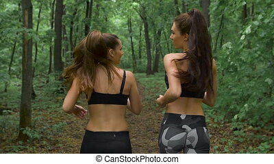 fitness workout outdoors. Two slender brunette with long hair running through the woods and communicate.