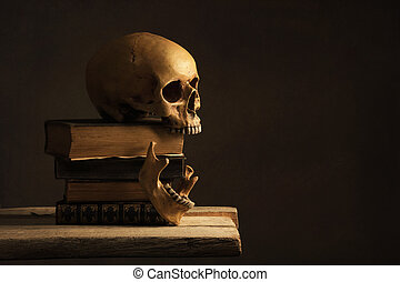 Human Skull with Jawbone on old Books