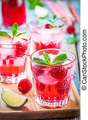 Raspberry mojito in a glass with mint and lime