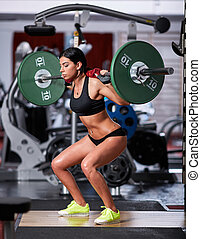 Woman doing squats with barbell on neck - Young woman doing...