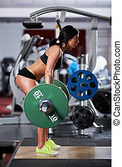 Woman doing deadlift with barbell - Young woman doing...