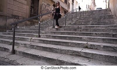 Young brunette woman walking down stairs.