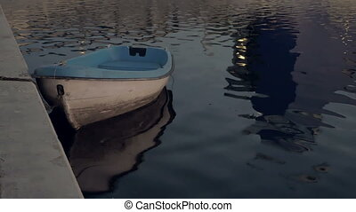 Boat on the water at the quay moorage at sunset - Boat at...