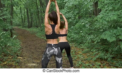Train in the forest. Two young and beautiful female athletes...