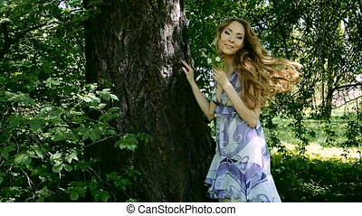 woman with long hair outdoors, turns to the camera
