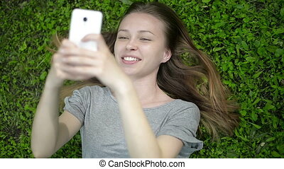 Girl lying on green meadow on cellphone