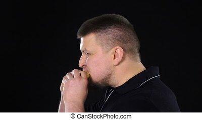 Man eating hamburger. Unhealthy diet. Food. Black. Slow motion