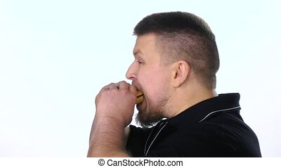 Young man eating a cheeseburger. White. Slow motion - Young...