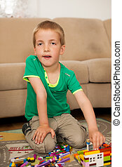 young boy playing with blocks on the ground in living room
