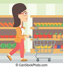 Customer with trolley - A woman pushing an empty supermarket...