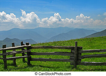 View of Smoky Mountains with fence in foreground.