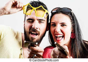 thrilled couple taking mobile photographs and selfies -...