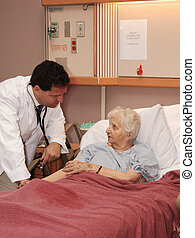 attending to senior woman in hospic - doctor visiting senior...