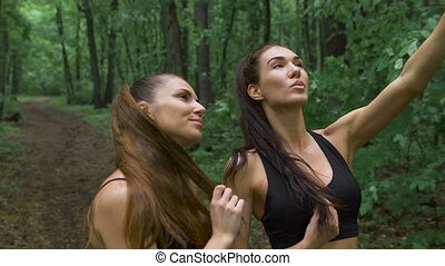 Two attractive girls fitness, make selfie on a smartphone....