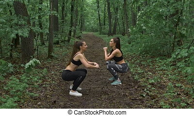 Train in the forest. Two young and beautiful female athletes do warm-up before an intense load.