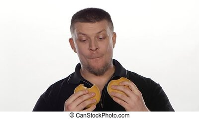 Man eats a cheeseburgers. White - Man eats a cheeseburgers,...
