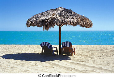 palapa on the beach - tiki umbrella with two Adirondack...