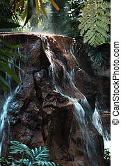 large rock waterfall - water falling off large rock...
