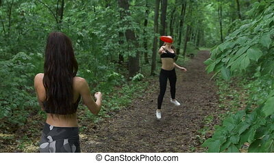 Two slender brunette in the woods, throwing a frisbee plate. They are having fun and playing on the footpath.