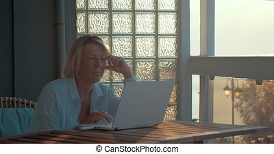 Mature Woman with Laptop on the Balcony - Mature woman is...