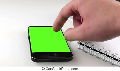 man hand using a smart phone in the office near drink coffee with chroma key, green screen, lifestyle communication with smartphone technology concept