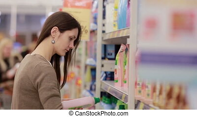 Woman chooses household chemicals in the store