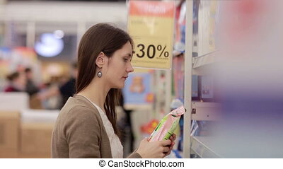 Woman chooses household chemicals in the store - young woman...