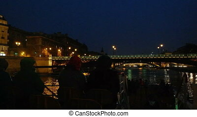 PARIS, FRANCE - 24 MARCH, 2016: Seine River cruise on boat tour. Tourists on the deck of the ship photographed night Paris