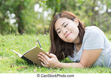 Asian woman writing a book in the garden