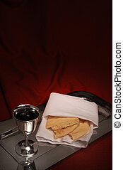 communion cup and bread on red fabric