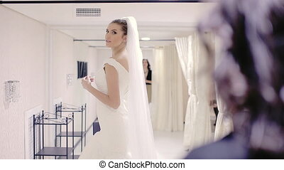 Wedding Dress Fitting in Bridal store - girl bride in...