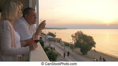 Couple drinking wine and looking at resort from balcony