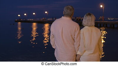 Senior couple in love by the sea at night - Senior couple...