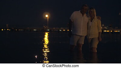 Couple watching candles sailing on water - Mature couple...
