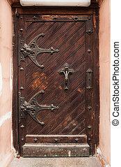 old wooden door with metal canopies in historical building