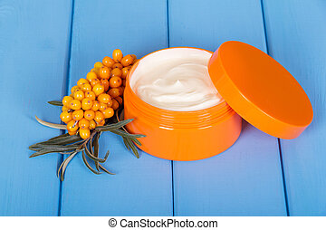 Bank with sea buckthorn cream on a blue background