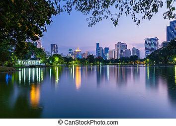 Bangkok skyline at dusk, Lumpini Park, Bangkok, Thailand -...