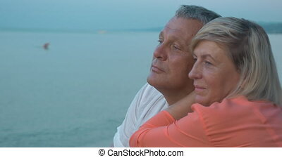 Senior couple in love - Woman embracing a man and they both...