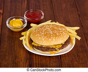 Hamburger, french fries and sauces on  background of dark wood