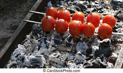 Tomatoes are cooking on coals. Outdoors video.