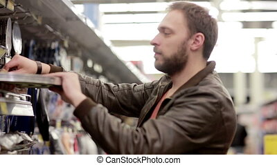 Man chooses sporting goods in store - The young man chooses...