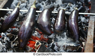 Eggplants are cooking on coals.