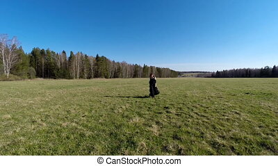 The girl walks across the field. Aerial view