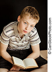 Lonely child sitting and reading a book - Lonely child with...
