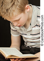 Single boy sitting and reading a book - Single child wearing...