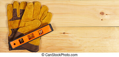 Level and gloves wrench on wooden background - Set of...