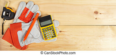 Calculator, pencil and gloves wrench on wooden background -...