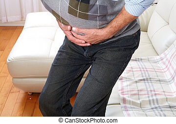 Man suffering from belly-ache - Unhappy man suffering from...