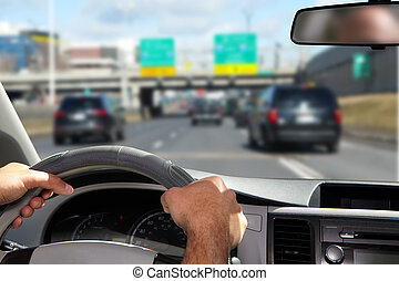 Man holding the steering wheel in a car
